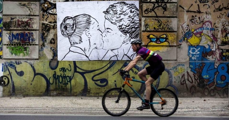 28.set.2014 - Ciclista passa em frente a cartaz com desenho com as candidatas à Presidência Marina Silva (PSB) e Dilma Rousseff (PT) se beijam em um muro no Rio de Janeiro, neste domingo