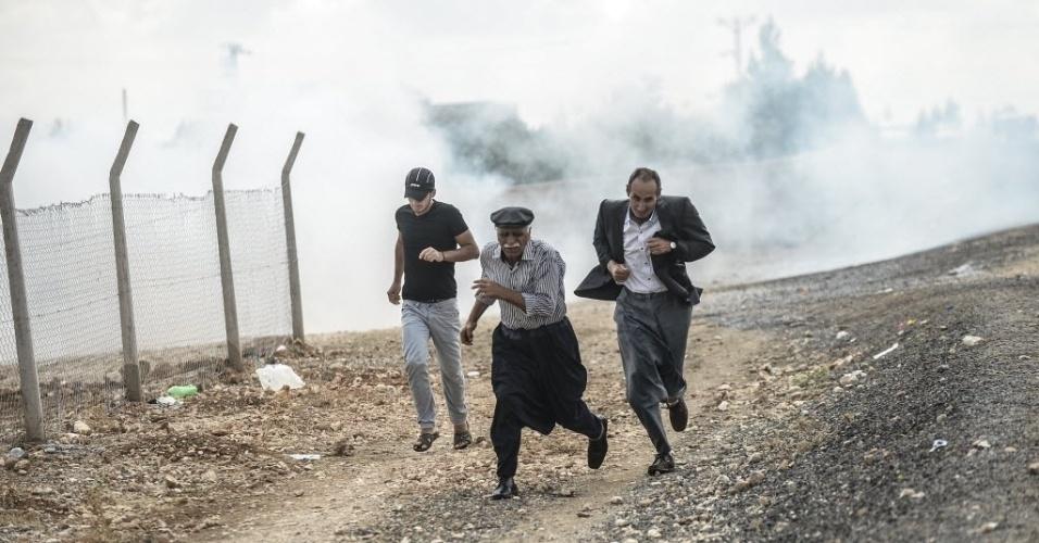 29.set.2014 - Homens fogem de ataques na cidade de Kobani, território sírio perto da fronteira entre a Síria e a Turquia, nesta segunda-feira (29). Centenas de curdos sírios fugiram para a Turquia para se proteger dos ataques do grupo Estado islâmico (EI) na Síria, porém, uma parcela de refugiados quer voltar para solo sírio para poder proteger suas casas e se juntar aos militantes locais que querem combater o EI