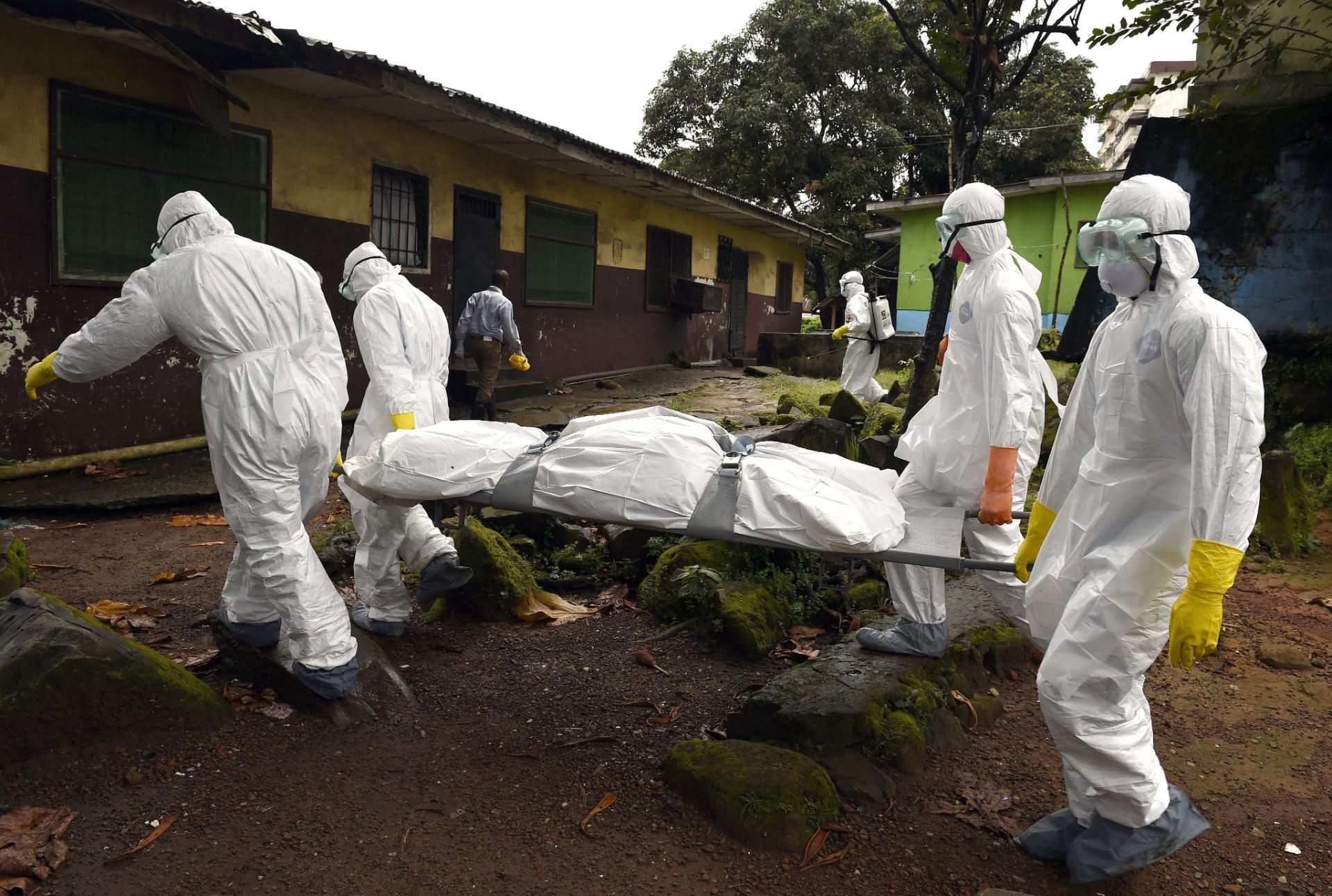 29.set.2014 - Membros da Cruz Vermelha carregam corpo de vítima do vírus ebola ao retirá-lo de sua casa em Monróvia, na Libéria