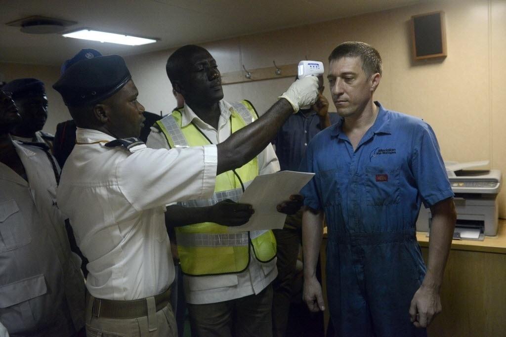 29.set.2014 - Oficiais de saúde da Nigéria verificam a temperatura corporal de um marinheiro ucraniano para verificar se há sinais do vírus ebola no porto Apapa, em Lagos, nesta segunda-feira (29)