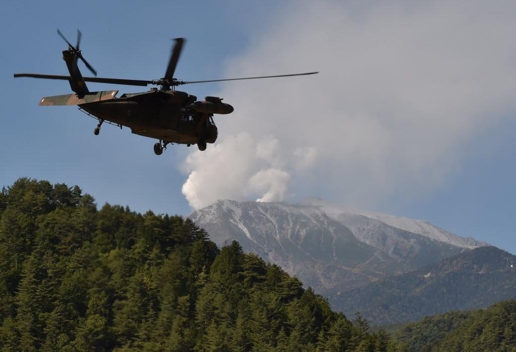 29.set.2014 - Um helicóptero militar deixa o local de pouso durante operação de resgate no Monte Ontake, em Otaki, Nagano, no Japão, nesta segunda-feira (29). As equipes reiniciaram a busca por sobreviventes após a erupção do vulcão do Monte Ontake, que deixou mais de 30 mortos. Centenas de pessoas caminhavam pela montanha quando o vulcão entrou em erupção. A maioria conseguiu sair com segurança, mas muitos foram atingidos pela chuva de rochas e cinzas e nuvens de gás tóxico lançadas pelo vulcão