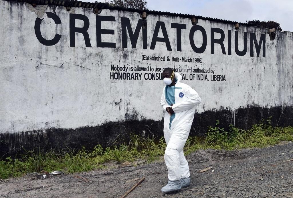 29.set.2014 - Um membro da equipe médica com roupas de proteção passa por crematório destinado às vítimas do ebola, em Monróvia, na Libéria, nesta segunda-feira (29). Segundo a OMS (Organização Mundial de Saúde), a Libéria é o país mais atingido pelo vírus, pois 3.458 pessoas foram infectadas e, entre elas, 1.830 morreram