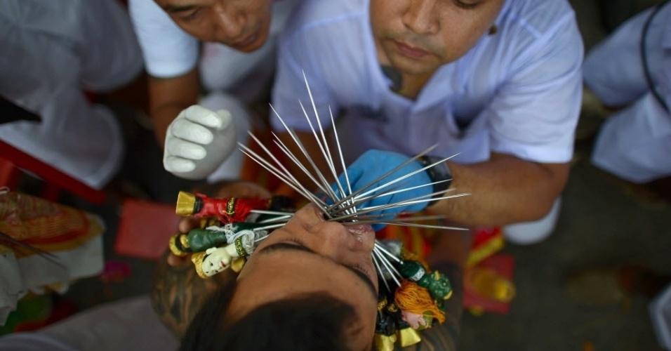 29.set.2014 - Agulhas de metal são inseridas no rosto de devoto durante rituais de autoflagelação do Festival Anual Vegetariano, que acontece em Pukhet, no sul da Tailândia