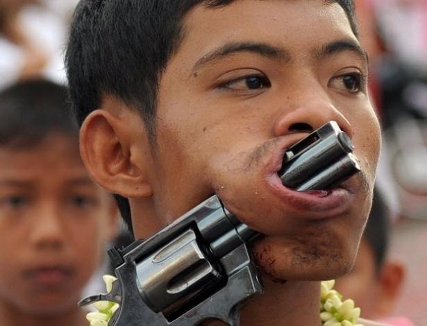 29.set.2014 - Devoto com pistolas com os canos atravessados nas bochechas participa durante a procissão do Festival Vegetariano, Pukhet, na Tailândia, nesta segunda (29)