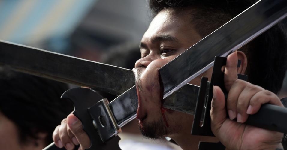 29.set.2014 - Devoto do Chinese Bang Neow Shrine com espadas atravessando suas bochechas participa da procissão do festival, que acontece em Pukhet, no sul da Tailândia