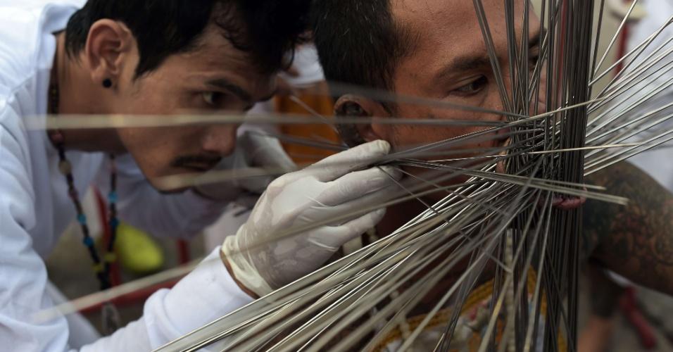 29.set.2014 - Devoto no local de adoração Chinese Bang Neow Shrine insere agulhas de metal nas bochechas durante a procissão do Festival Vegetariano da cidade de Pukhet, no sul da Tailândia, nesta segunda-feira (29).