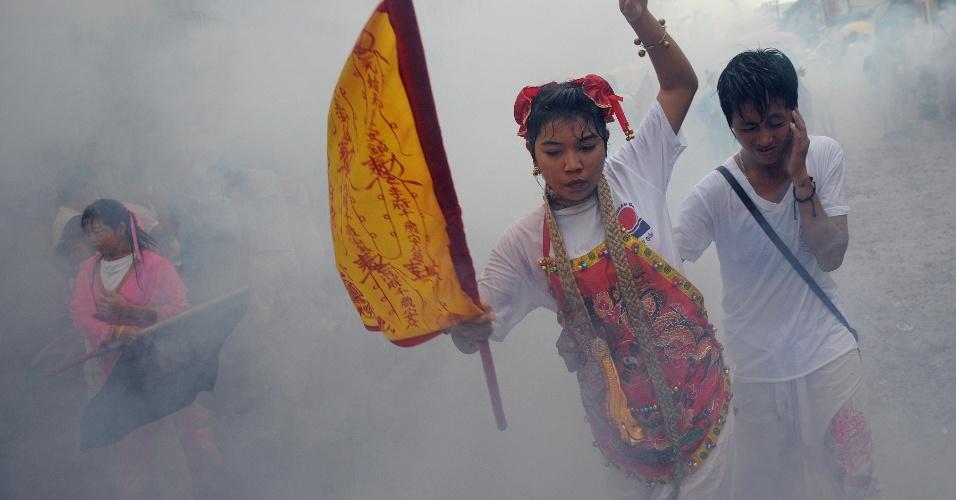 29.set.2014 - Devotos andam entre nuvens de fumaça, durante procissão do Festival Vegetariano, em Phuket, na Tailândia