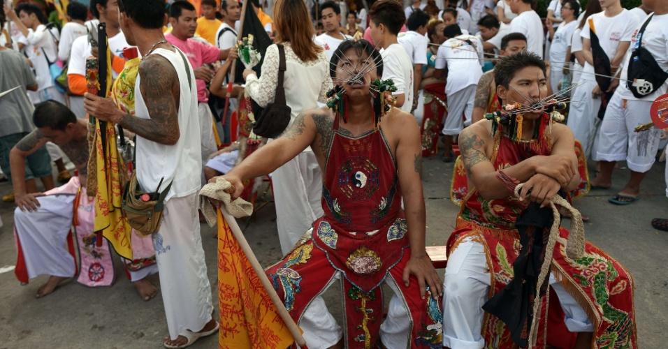 29.set.2014 - Devotos do Chinese Bang Neow Shrine com agulhas de metal atravessadas nas bochechas esperam o começo da procissão durante o Festival Anual Vegetariano em Pukhet, no sul da Tailândia