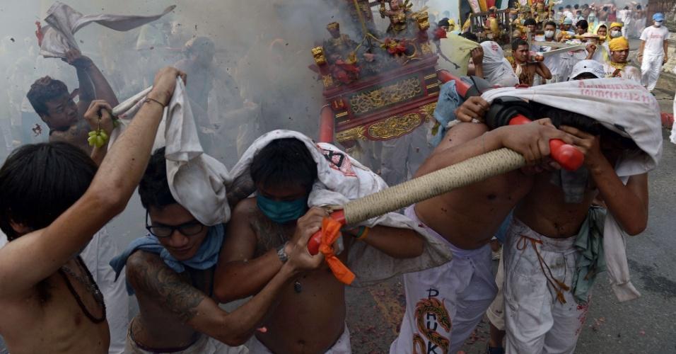 29.set.2014 - Devotos no local de adoração Chinese Bang Neow Shrine se protegem de fogos de artifício, durante procissão do Festival Vegetariano da cidade de Pukhet, no sul da Tailândia, nesta segunda-feira (29). Durante o festival, que começa toda primeira noite da nona lua e termina nove dias depois, os devotos se martirizam com espadas, furam suas bochechas com objetos afiados e cometem outros atos de automutilação para se purificarem e limparem os pecados da comunidade.