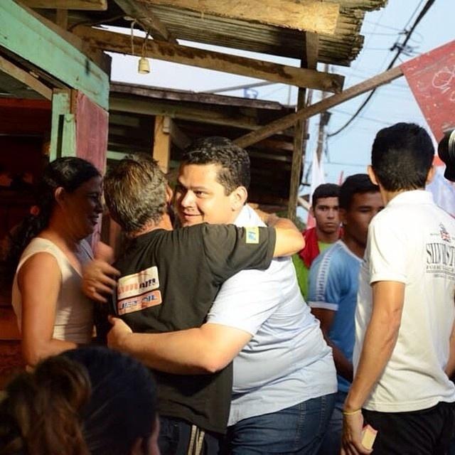 20.set.2014 - Candidato a senador pelo Amapá, Davi Alcolumbre (DEM) (ao centro com camisa azul clara) abraça eleitor durante caminhada nos bairros Murici e Vale Verde, em Macapá