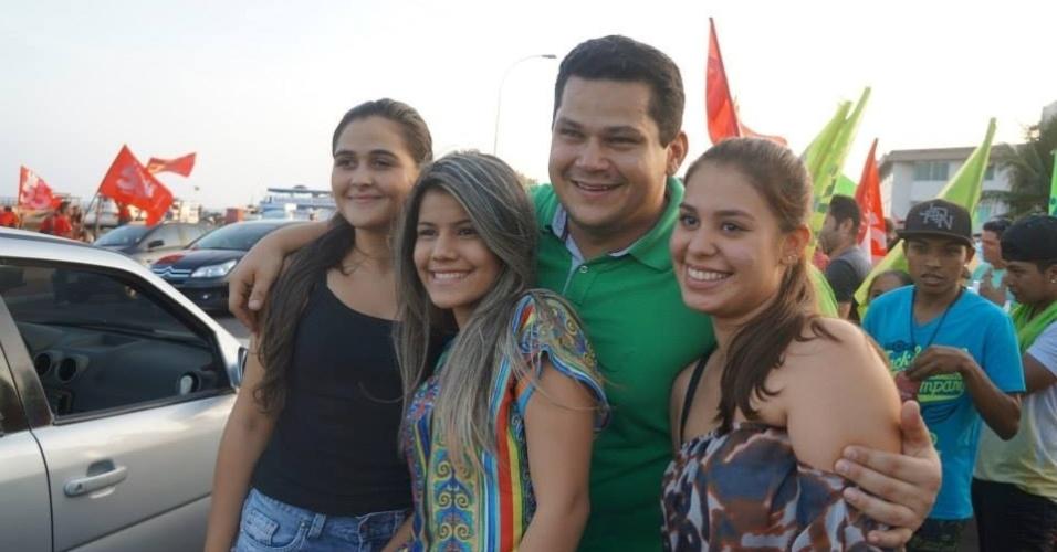 24.set.2014 - Candidato a senador pelo Amapá, Davi Alcolumbre (DEM) tira fotos com eleitoras durante caminhada pela orla do rio Amazonas, em Macapá
