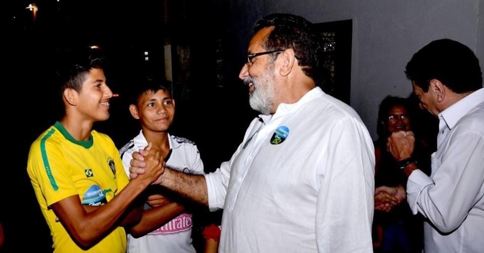 24.set.2014 - Candidato a senador pelo Amapá, Gilvam Borges (PMDB) (à dir. com camisa branca) aperta a mão de eleitor durante uma caminhada no Igarapé da Fortaleza, em Macapá