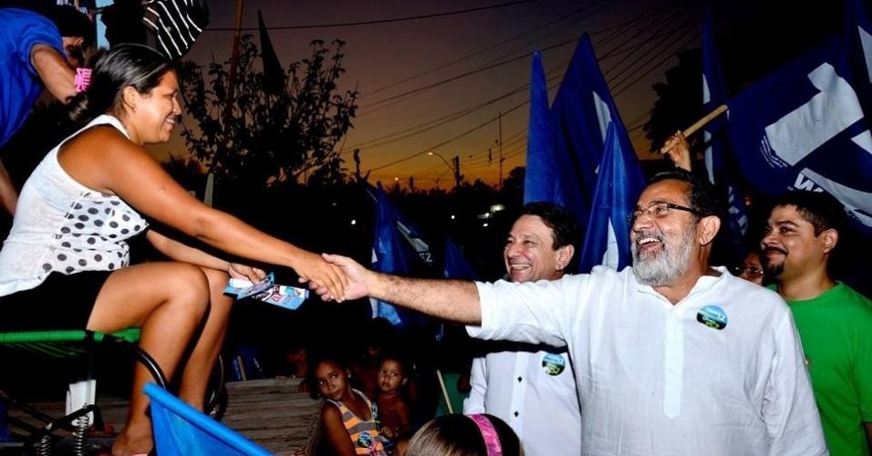 24.set.2014 - Candidato a senador pelo Amapá, Gilvam Borges (PMDB) (à dir. com camisa branca) aperta a mão de eleitora durante uma caminhada no Igarapé da Fortaleza, em Macapá