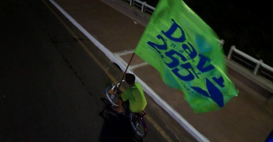 24.set.2014 - Eleitor com bicicleta passeia com bandeira do candidato a senador pelo Amapá Davi Alcolumbre (DEM), durante caminhada pela orla do rio Amazonas, em Macapá