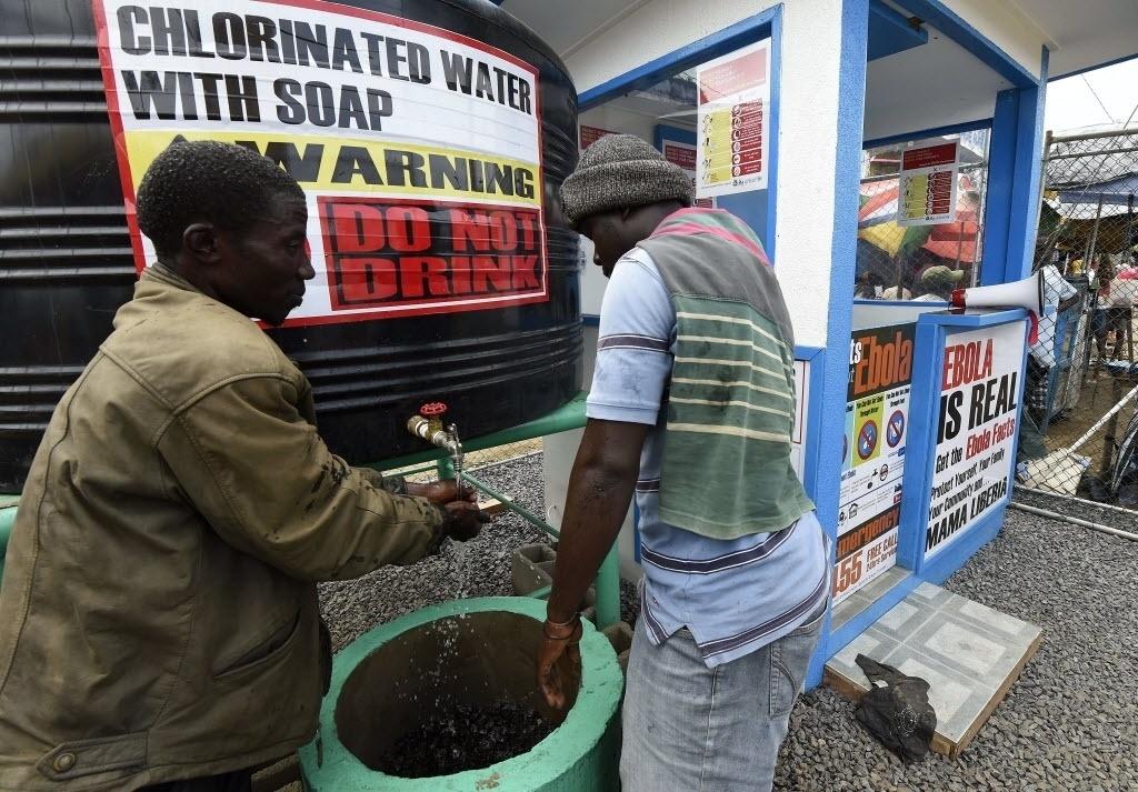 30.set.2014 - Dois homens lavam as mãos em uma estação de informação e saneamento que trabalha pela conscientização sobre o vírus ebola em Monróvia, na Libéria, nesta terça-feira (30). A Libéria foi um dos países mais afetado pelo epidemia. Cerca de 3,7 mil crianças já perderam pelo menos um dos pais desde o início do surto de ebola na África Ocidental, anunciou o Fundo da ONU para a Infância, Unicef. Em nota, emitida esta terça-feira, a agência informa que várias delas são rejeitadas pelos familiares. A Libéria, a Serra Leoa e a Guiné Conacri são os países mais afetados pela doença, que já fez mais de 3 mil mortos