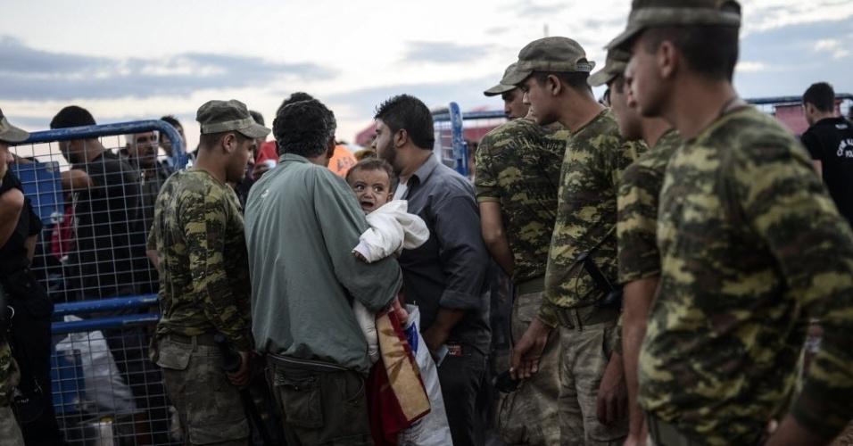 30.set.2014 - Sírios curdos chegam na fronteira entre a Síria e a Turquia depois que vários morteiros atingiram ambos os lados, perto da cidade de Suruc, na província de Sanliurfa, na segunda-feira (29) - a foto só foi divulgada nesta terça-feira (30). Milhares de curdos sírios fugiram para a Turquia por conta dos ataques do Estado Islâmico (EI)