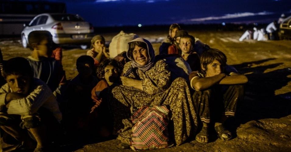 30.set.2014 - Uma família curda da Síria é fotografada após atravessar a fronteira entre o seu país e a Turquia depois que vários morteiros atingiram ambos os lados, perto da cidade de Suruc, na província de Sanliurfa, na segunda-feira (29) - a foto só foi divulgada nesta terça-feira (30). Milhares de curdos sírios fugiram para a Turquia por conta dos ataques do Estado Islâmico (EI)