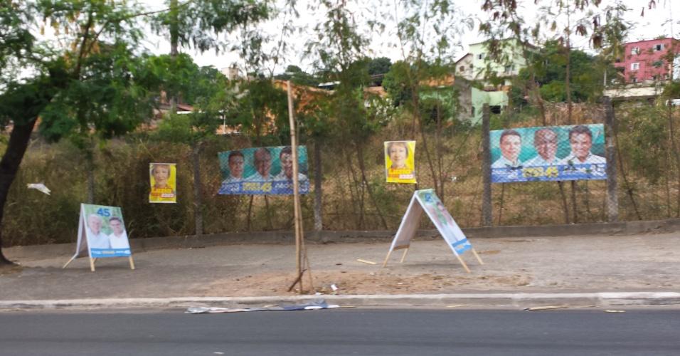 30.set.2014 - Em Belo Horizonte, propaganda política espalhadas por calçada atrapalham a passagem de pedestres. Cercas em terrenos privados não escapam do apetite propagandístico dos candidatos mineiros
