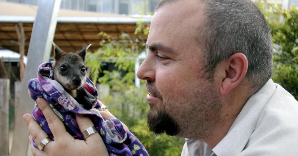 1º.out.2014 - Funcionário do zoológico Taronga, em Sydney, cuida do filhote órfão de canguru chamado Akira