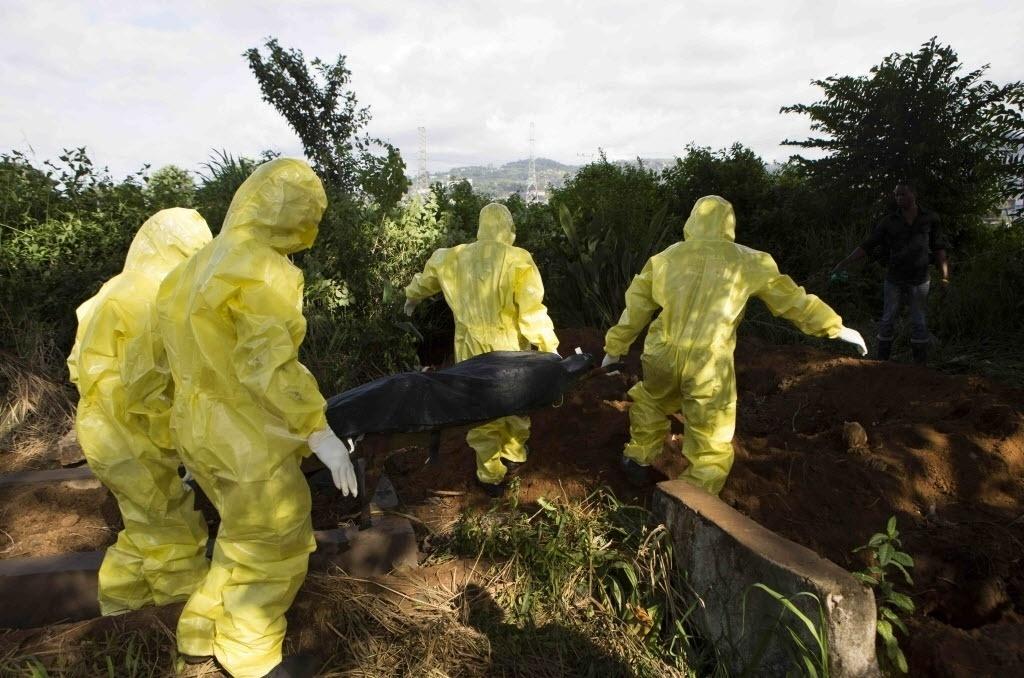 1º.out.2014 - Homens enterram corpo de vítima de ebola usando roupas e acessórios de proteção durante sepultamento em Freetown, Serra Leoa. O país, a Guiné, Libéria e Nigéria são os países mais afetados pela doença
