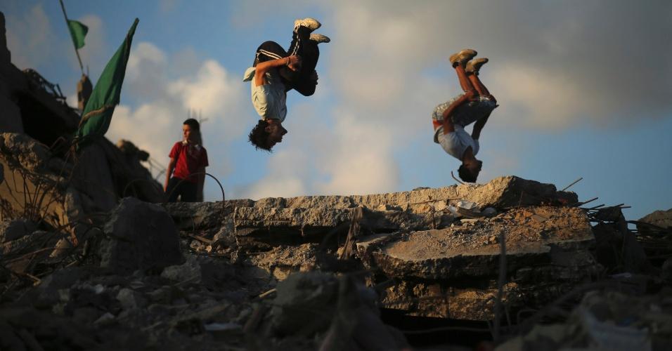 1º.out.2014 - Jovens palestinos praticam Parkour sobre as ruínas de casas que foram destruídas nas sete semanas de ofensiva israelense, em Gaza. Parkour é uma atividade focada na superação de obstáculos