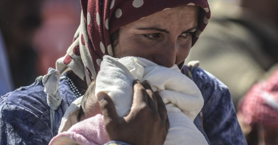 1º.out.2014 - Uma mulher curda síria segura seu filho enquanto aguarda para poder atravessar a fronteira entre a Síria e a Turquia, na cidade de Suruc, na província de Sanliurfa, nesta quarta-feira (1º). Dezenas de milhares de sírios podem ser forçados a fugir de sua terra natal, já devastada por uma guerra civil, se o Estado Islâmico (EI) continuar a ganhar terreno, disse Valerie Amos, chefe da agência humanitária da Organização das Nações Unidas (ONU).
