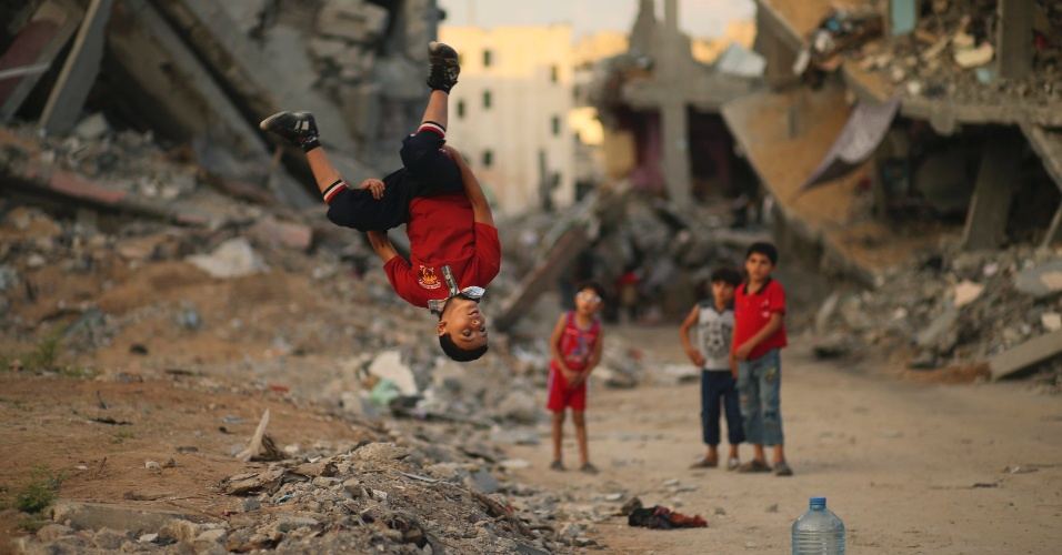 1°.out.2014 - Jovens palestinos praticam Parkour sobre as ruínas de casas que foram destruídas nas sete semanas de ofensiva israelense, em Gaza. Parkour é uma atividade focada na superação de obstáculos