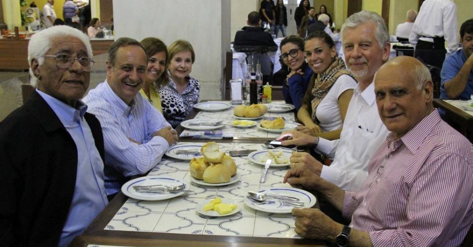 29.set.2014 - O candidato do PDT Lasier Martins (direita) ao Senado pelo Rio Grande do Sul participa de almoço no Mercado Público, em Porto Alegre, com sua equipe de campanha
