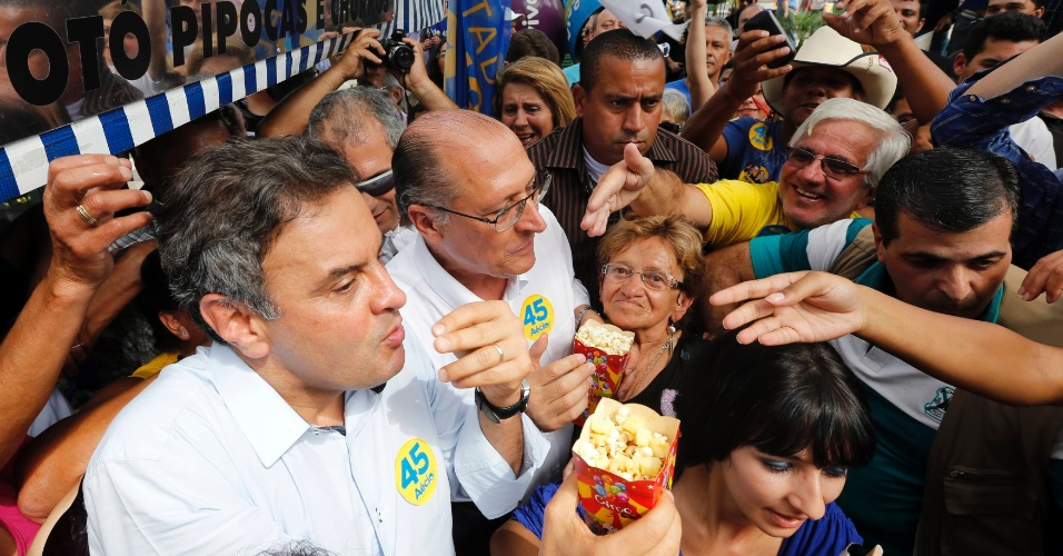 30.set.2014 - O candidato à Presidência Aécio Neves (PSDB) come pipoca ao lado do candidato à reeleição em São Paulo, governador Geraldo Alckmin (PSDB), durante caminhada em Mogi das Cruzes, região metropolitana da capital. O presidenciável tucano disse estar animado com o resultado das pesquisas divulgadas entre ontem e hoje, e disse que volta ao Estado a partir do dia 6 de outubro, para a campanha do segundo turno