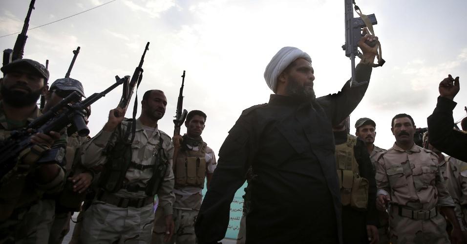 2.out.2014 - Combatentes xiitas iraquianos de Tal Afar, leais ao aiatolá Ali al-Sistani, levantam as suas armas na cidade de Karbala, no centro do Iraque. O grupo faz parte da ofensiva contra os jihadistas do Estado Islâmico, grupo que invadiu grande parte sunita do país em junho