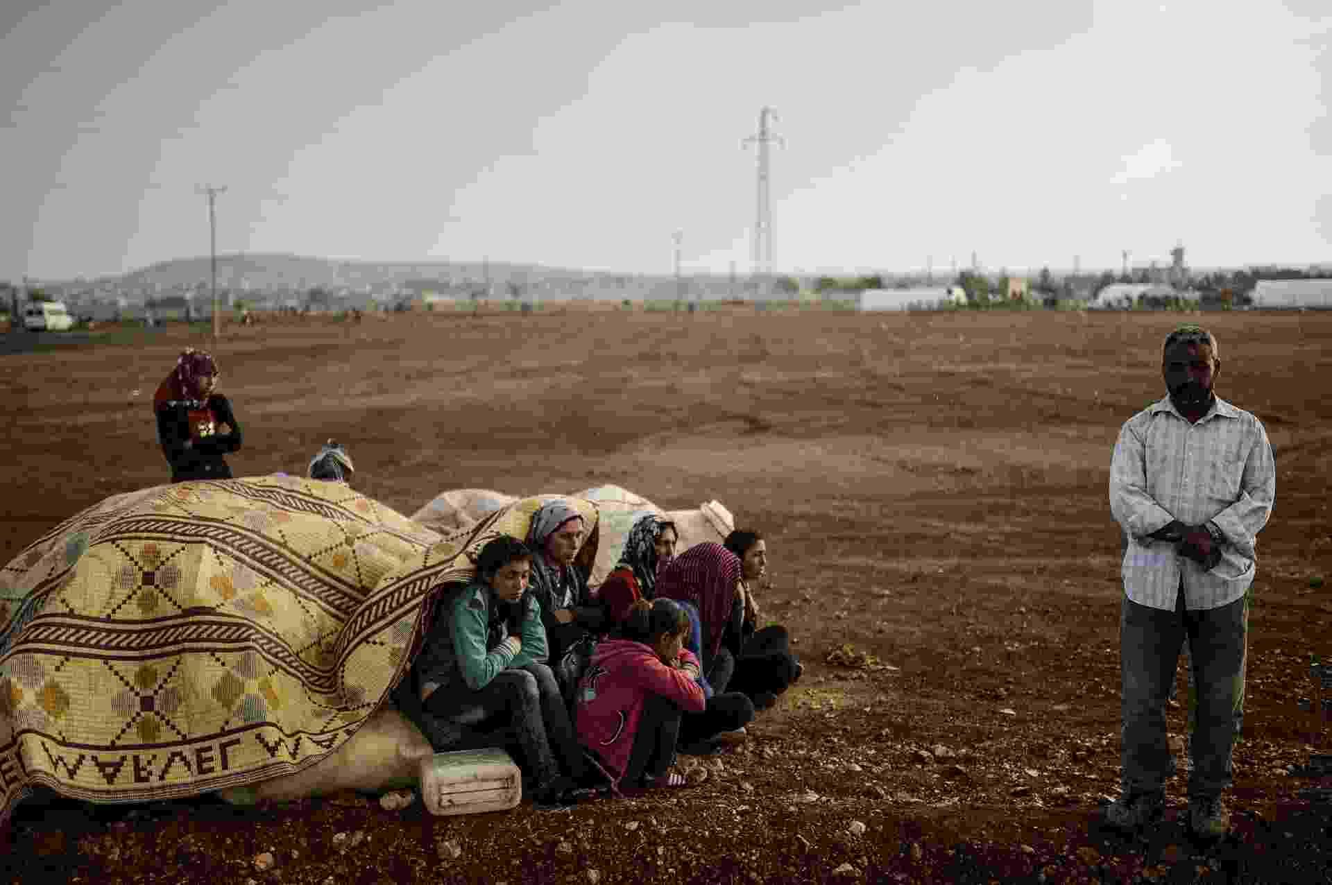 2.out.2014 - Curdos sírios se encondem da chuva na província de Sanliurfa, depois de cruzar a fronteira entre a Síria e a Turquia. Combatentes do Estado Islâmico estão empurrando o conflito em direção a uma cidade curda na fronteira da Síria com Turquia - Bulent Kilic/AFP