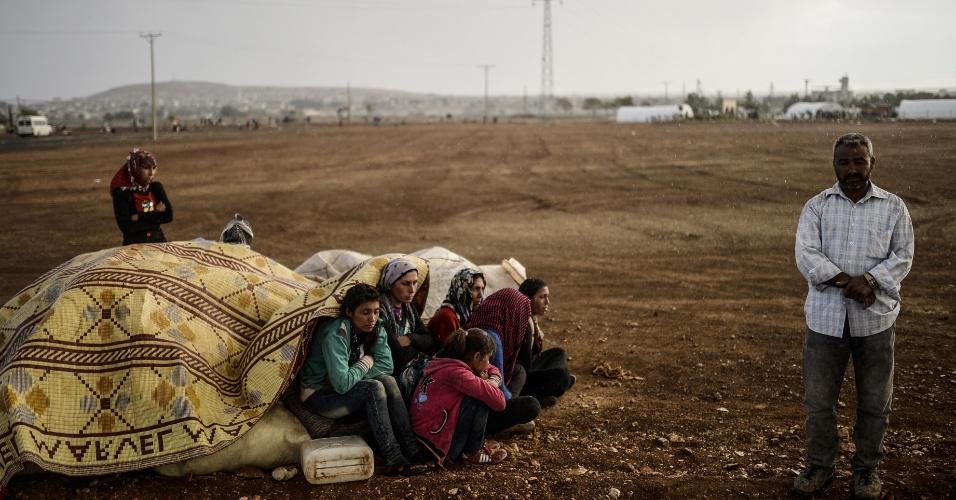 2.out.2014 - Curdos sírios se encondem da chuva na província de Sanliurfa, depois de cruzar a fronteira entre a Síria e a Turquia. Combatentes do Estado Islâmico estão empurrando o conflito em direção a uma cidade curda na fronteira da Síria com Turquia
