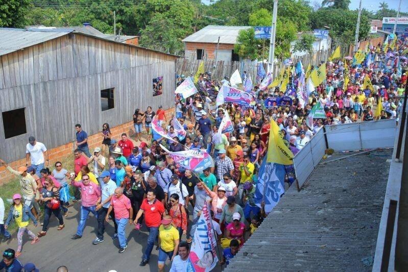 2.out.2014 - Governador e candidato a reeleição no Amazonas do Pros, José Melo (de vermelho, no primeiro plano à direita), caminha puxando a passeata de sua campanha, no bairro de Governador Melo, em Parintins