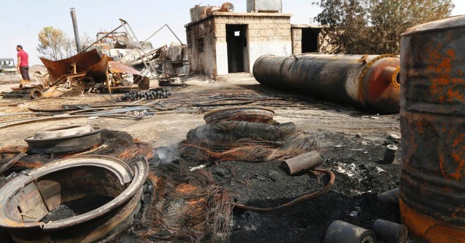 2.out.2014 - Homem inspeciona danos em uma refinaria de petróleo e um posto de gasolina que foram alvos de ataques de aeronaves dos Estados Unidos em Raqqa, na Síria. O ataque faz parte de uma tentativa de enfraquecer o Estado Islâmico. A estratégia é danificar e destruir as bases e forças do grupo que conquistou grandes áreas no Iraque e na Síria