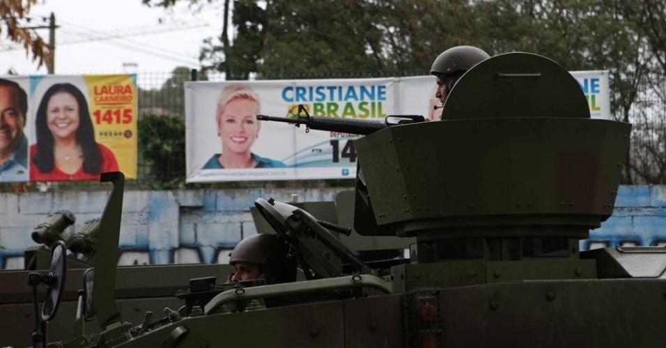 2.out.2014 - Soldados do Exército fazem patrulha na comunidade Vila do João, no Complexo da Maré, zona norte do Rio de Janeiro, perto de cartazes de campanha eleitoral. No início da semana, um jovem de aproximadamente 18 anos morreu após troca de tiros entre traficantes de facções rivais na Maré