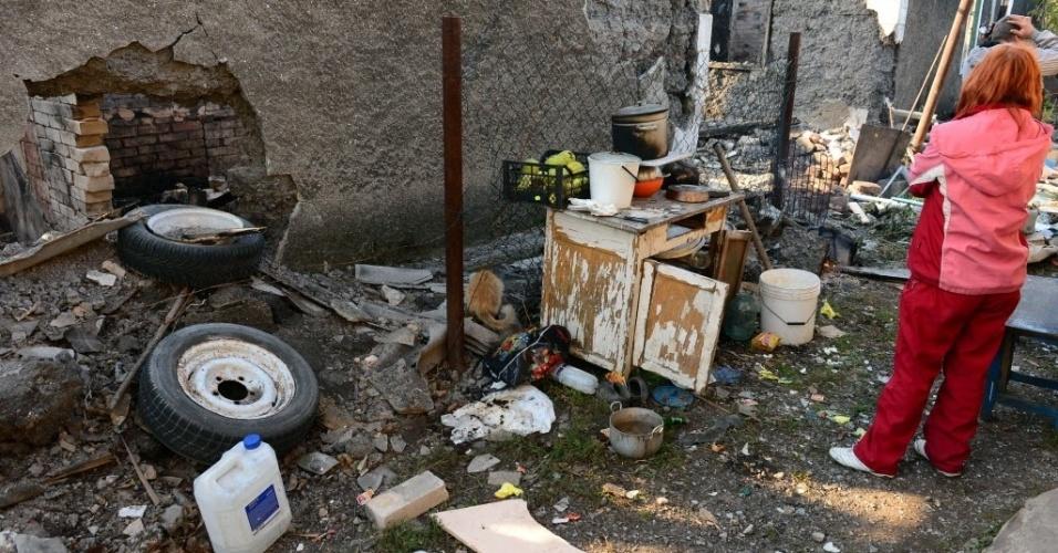 2.out.2014 - Um morador mostra ondeuma bomba caiu destruindo sua casa no distrito de Oktyabrsky, em Donetsk, na Ucrânia, ao lado do aeroporto local nesta quinta-feira (2). As autoridades da Ucrânia e os rebeldes pró-Rússia dizem ambos ter o controle sobre o aeroporto da cidade de Donetsk, no leste do país, onde os combates que começaram nesta manhã continuam, segundo reconheceram os dois grupos.As milícias separatistas lançaram no começo da manhã um ataque contra o aeroporto. Os rebeldes atacaram quatro vezes as posições ucranianas dentro do aeroporto durante o dia de ontem, e segundo o porta-voz das forças de Kiev, Vladislav Selezniov, chegaram a tomar um de seus dois terminais, embora depois tenham sido expulsos do prédio pelos paraquedistas ucranianos