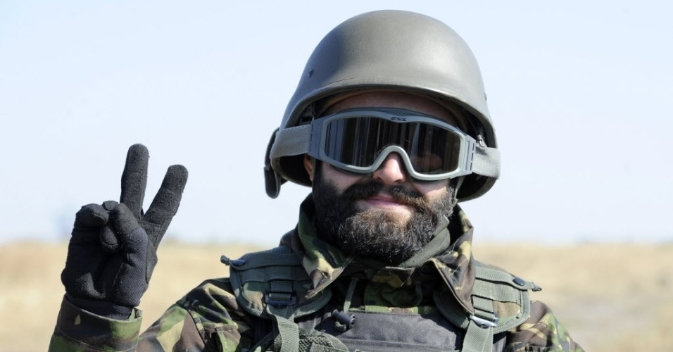2.out.2014 - Um soldado do batalhão pró-ucrânia faz o sinal de paz e amor durante um exercício militar perto da cidade ucraniana de Mariupol nesta quinta-feira (2)