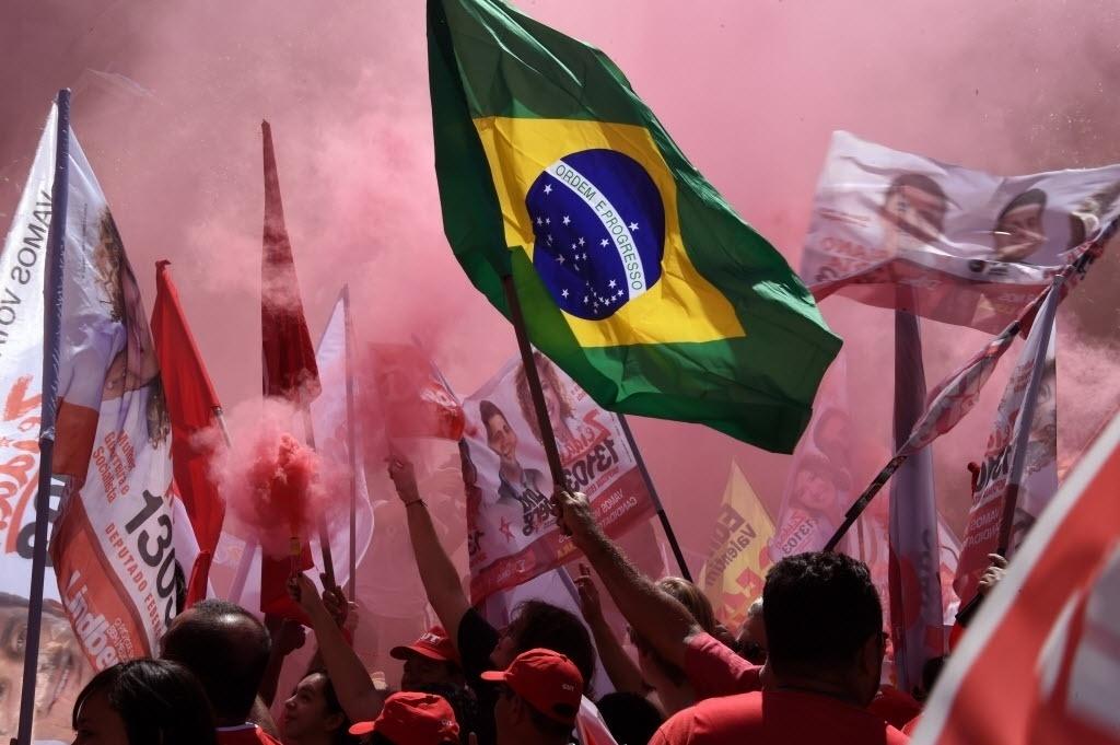 15.set.2015 - Apoiadores da presidente e candidata à reeleição Dilma Rousseff (PT) fazem manifestação contra a corrupção na Petrobras na frente da sede da estatal no Rio de Janeiro. As primeiras suspeitas sobre a existência de um esquema de corrupção dentro da Petrobras começaram em março, quando a Polícia Federal deflagrou a operação Lava-Jato e prendeu, entre outras pessoas, o doleiro Alberto Yousseff e o ex-diretor de Abastecimento da estatal Paulo Roberto Costa. A Polícia Federal estima que o esquema tenha desviado em torno de R$ 10 bilhões. A PF acredita que parte do dinheiro recebido por Paulo Roberto a título de propina tenha sido posteriormente direcionado a políticos da base aliada do PT