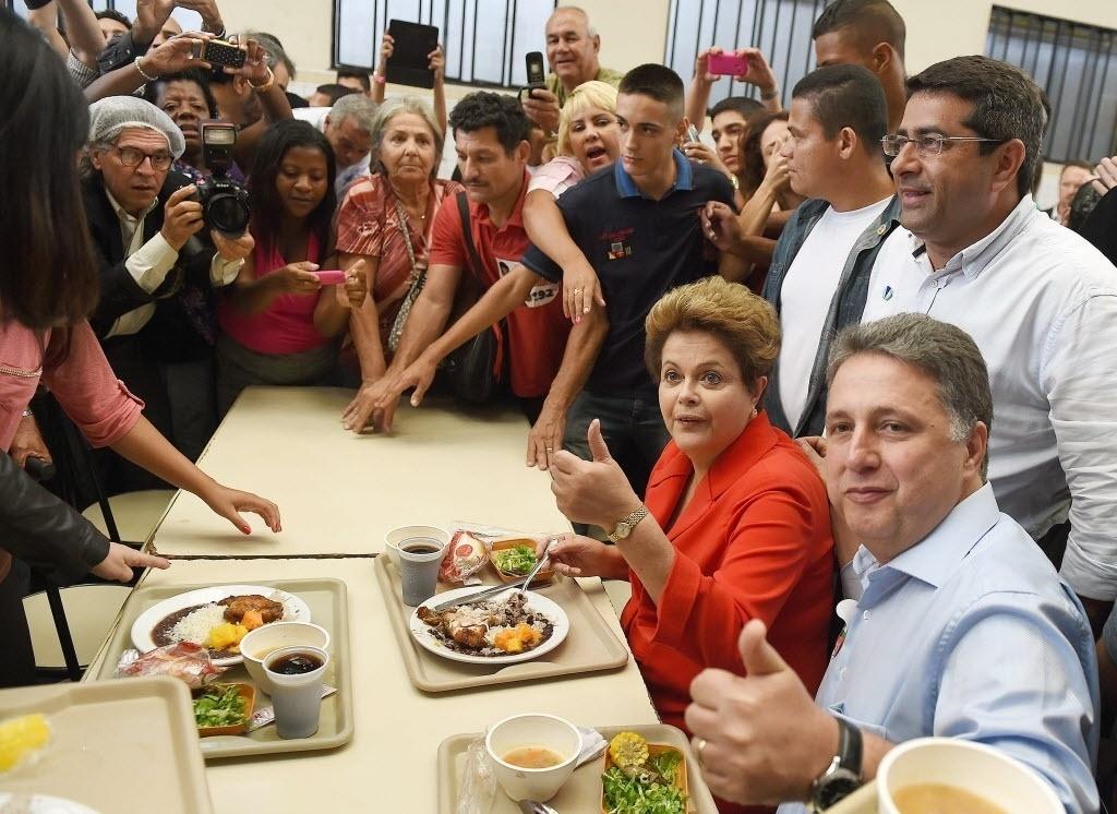 27.ago.2014 - A presidente e candidata à reeleição Dilma Rousseff (PT) almoça com o candidato do PR ao governo do Rio de Janeiro, Anthony Garotinho, em restaurante popular no Rio de Janeiro