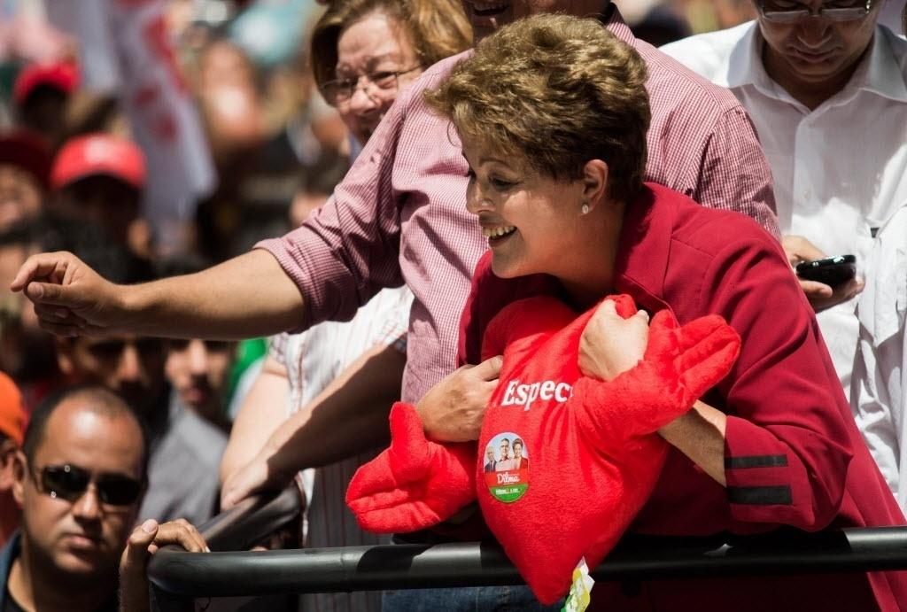 """3.out.2014 - A presidente e candidata à reeleição Dilma Rousseff (PT) ganha de um eleitor um coração de pelúcia durante carreata em São José dos Campos. Dilma afirmou nesta sexta-feira que a acusação de uso da máquina pública em sua campanha parte de quem """"corre o risco de perder"""" a disputa. O presidenciável Aécio Neves (PSDB) tem acusado Dilma de usar os Correios a favor de sua reeleição. Segundo o tucano, a estatal deixou de entregar material de sua campanha em Minas Gerais"""