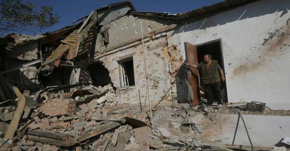 3.out.2014 - Anatoly Nosvo, 65, mostra como sua casa ficou danificada após bombardeio na última quinta-feira (2) na aldeia de Pisky, perto de Donetsk, na Ucrânia. A Ucrânia acusou as forças russas nesta sexta-feira (3) de ajudar os separatistas a aumentas a pressão sobre as tropas do governo ao bloquear o acesso e bombardear o principal aeroporto da cidade de Donetsk, ameaçando o frágil cessar-fogo da guerra