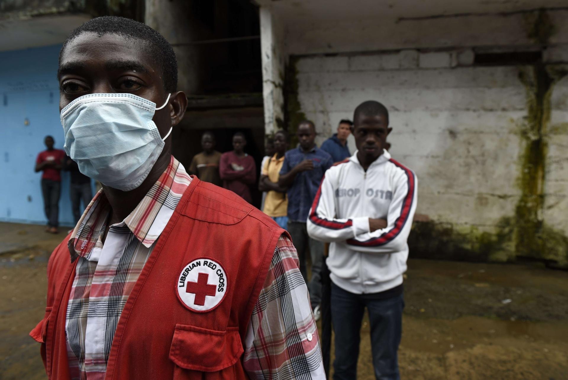 3.out.2014 - Funcionário da equipe da Cruz Vermelha procura pessoas mortas em Monrovia, capital da Libéria. O vírus paralisou os já fracos serviços de saúde do país e matou 89 trabalhadores de saúde. A Libéria registra mais da metade das mortes por ebola