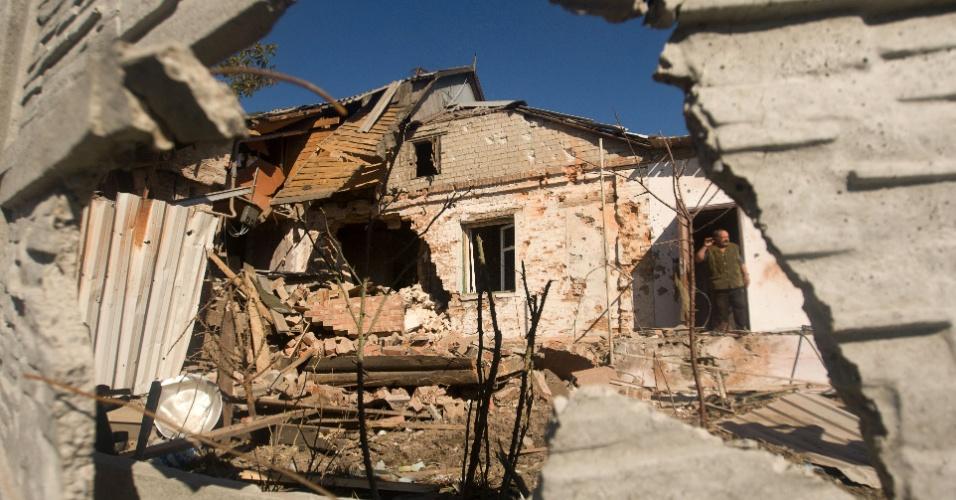 3.out.2014 - Homem anda entre os escombros de casas destruídas por bombardeios na aldeia de Peski, nos subúrbios de Donetsk, na Ucrânia. Tropas ucranianas e rebeldes pró-Rússia entraram em confronto nesta sexta