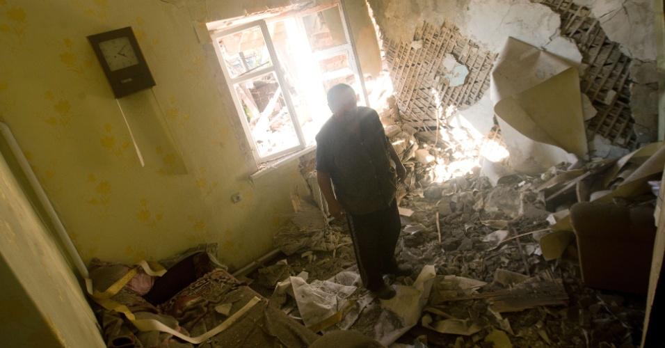 3.out.2014 - Homem anda sobre os escombros de uma casa destruída por bombardeios na aldeia de Peski, nos subúrbios de Donetsk, na Ucrânia. Tropas ucranianas e rebeldes pró-Rússia entraram em confronto nesta sexta