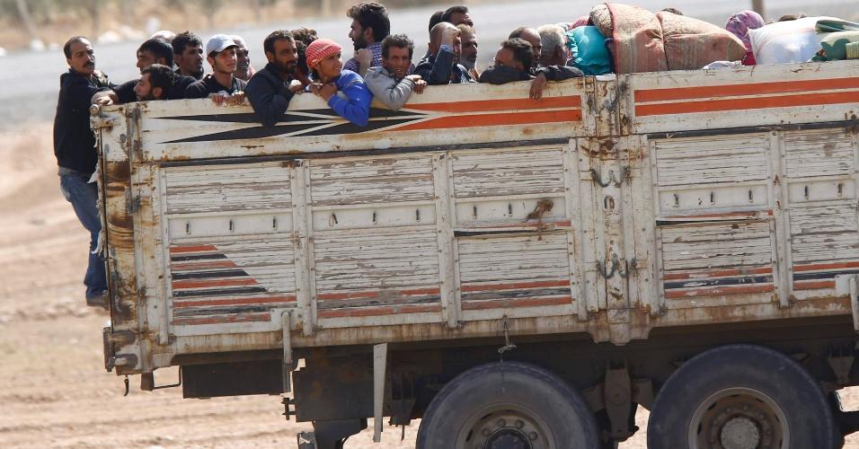 3.out.2014 - Refugiados curdos sírios se acomodam na carroceria de um caminhão depois de cruzar a fronteira e chegar até a Turquia. Combatentes curdos e representantes do Estado Islâmico entraram em confronto nesta sexta na fronteira entre a Síria e a Turquia. O governo da Turquia disse que iria fazer o que fosse possível para evitar que Kobani, uma cidade predominantemente curda, fique nas mãos do Estado Islâmico