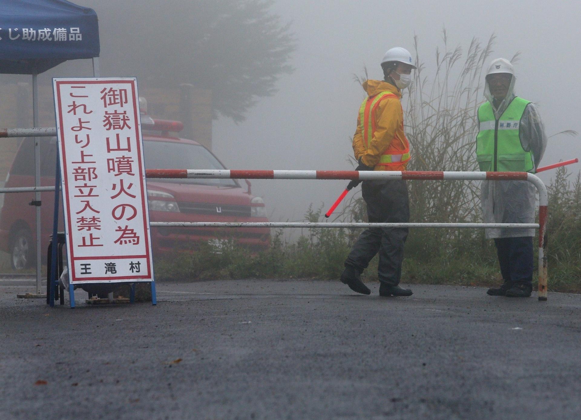 3.out.2014 - Seguranças fazem guarda em uma fechada prócima ao monte Ontake, no vilarejo de Otaki, próximo a Negano, no Japão, nesta sexta-feira (3). As autoridades japonesas informaram que 16 pessoas permanecem desaparecidas seis dias após a erupção do monte Ontake, o que deve ampliar o total de 47 mortes já confirmadas