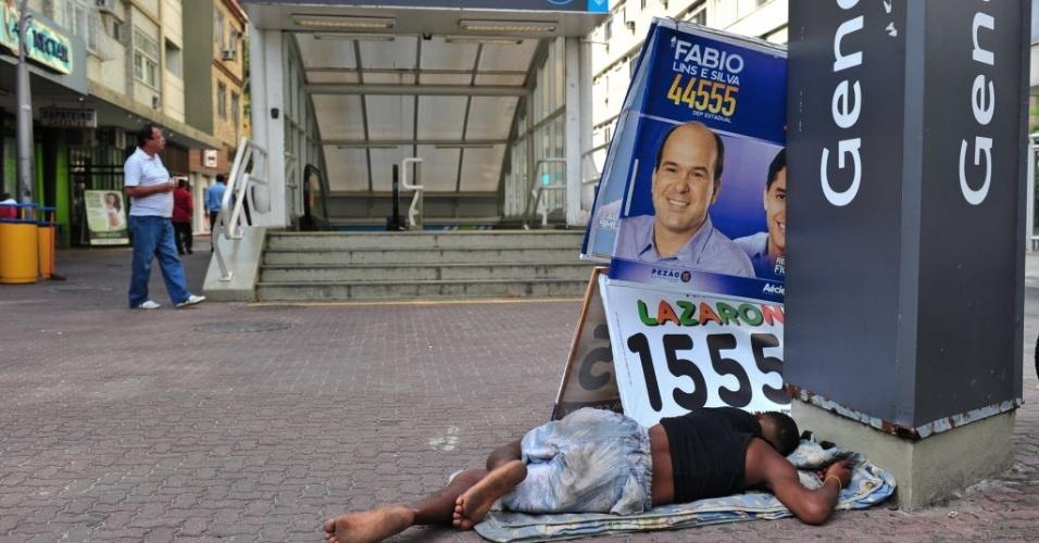 1.out.2014 - Morador de rua dorme ao lado de um cavalete político em frente à estação de metrô General Osório, em Ipanema, zona sul da cidade, na tarde desta quarta-feira (01/10)