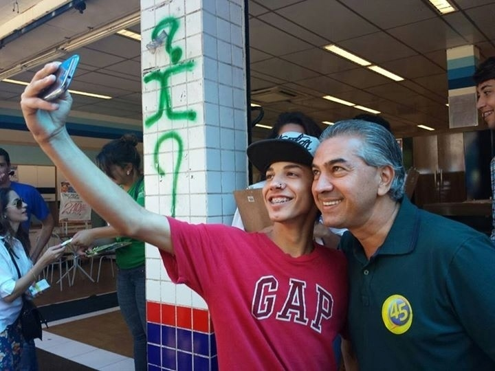 """4.out.2014 - O candidato à governados do Mato Grosso do Sul, Reinaldo Azambuja (PSDB), tirou """"selfies"""" com seus eleitores enquanto fazia uma caminhada no comércio de Campo Grande na manhã deste sábado (4), véspera da eleição"""