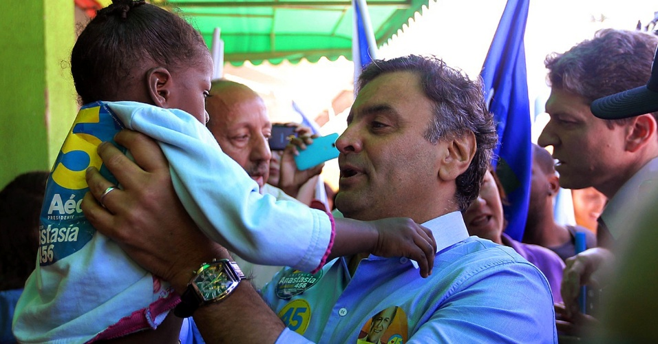 4.out.2014 - O candidato do PSDB à Presidência da República, Aécio Neves, ergue criança durante atividade de campanha em seu Estado natal, Minas Gerais, na manhã deste sábado (4). Ele participou de uma carreata ao lado do candidato de seu partido ao governo do Estado, Pimenta da Veiga, e do candidato ao Senado Antonio Anastasia, em Ribeirão das Neves, na região metropolitana de Belo Horizonte