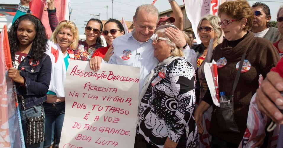 4.out.2014 - O candidato do PT ao governo do Rio Grande do Sul, Tarso Genro, fez corpo a corpo na manhã deste sábado (4) no bairro Humaitá, em Porto Alegre. Ele recebeu um cartaz de apoio feito pelos moradores da região
